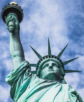 Statua wolności, widziana pod niskim kątem, z zachmurzonym tłem i niebieskim niebem, na liberty island w nowym jorku, usa.