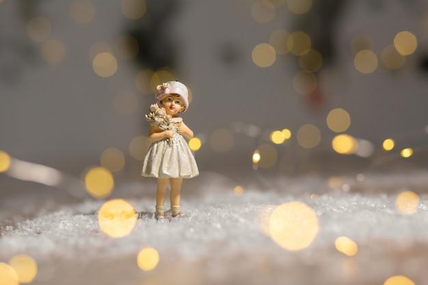 Statuetka dziewczyna świąteczny wystrój, ciepłe światła bokeh.