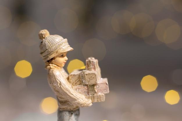 Statuetka dziewczyny trzymającej pudełka z prezentami na boże narodzenie w jej rękach świąteczny wystrój, ciepłe światła bokeh.