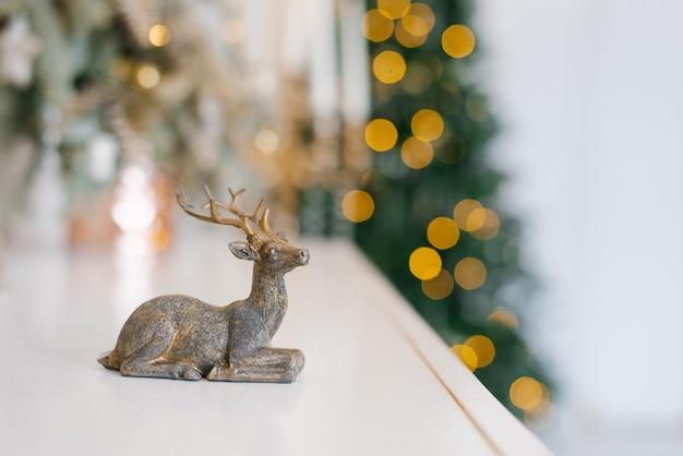 Statuetka jelenia na tle lampek choinkowych. karta noworoczna z miejsca na kopię