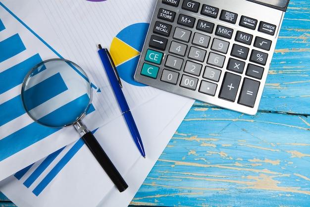 Statystyki, długopis, lupa i kalkulator na stole