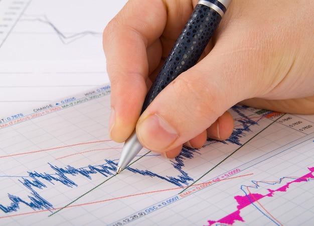 Statystyki finansowe dokumentują długopis infografiki przy stole urzędu