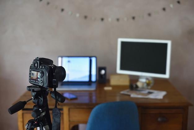 Statyw z aparatem fotograficznym i nieostrym stołem warsztatowym