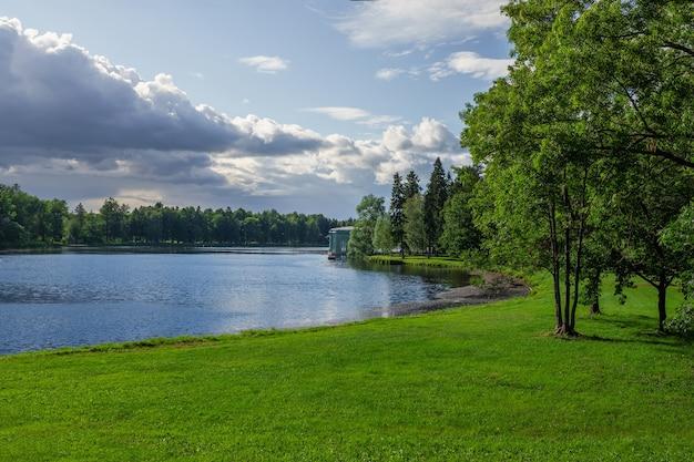 Staw z zielonym trawnikiem w jasny, słoneczny dzień. pawilon wenus w parku gatczyna. rosja.