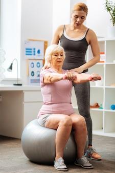 Stawanie się silniejszym. przyjemna starsza kobieta patrząca na swoje ręce podczas podnoszenia hantli