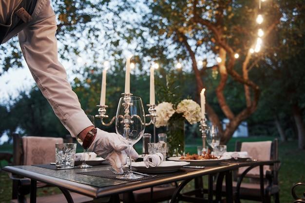 Stawia szklankę. ręka kelnera w rękawiczkach. pracownik jest zaangażowany w serwowanie stołu