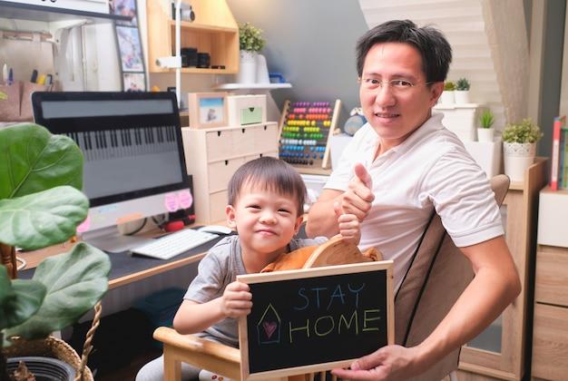 """Stay home stay safe, azjatycki chłopiec z przedszkola i jego pracujący w domu ojciec trzymają czarną tablicę z komunikatem """"zostań w domu"""", covid-19 pozostając w domu koncepcja"""