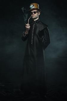 Steampunk mężczyzna w długim płaszczu pali fajkę.