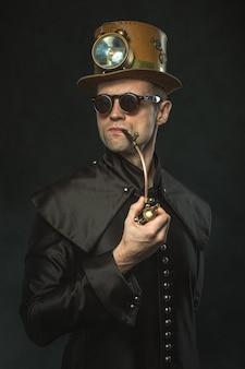 Steampunk mężczyzna w kapeluszu pali fajkę