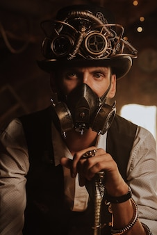 Steampunkowy cosplay. portret mężczyzny w cylindrze, okularach i masce gazowej