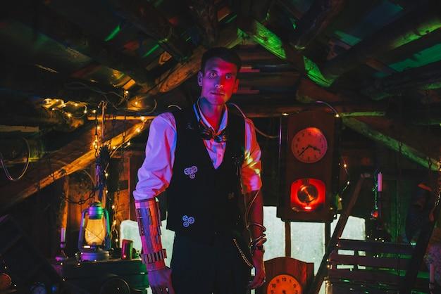 Steampunkowy cosplay. wynalazca mężczyzna w garniturze z zębatkami w warsztacie z neonowym światłem