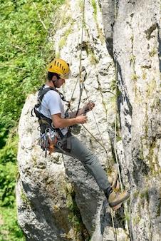 Steeplejack wspinający się po skalnej ścianie