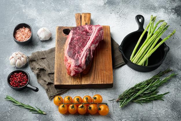 Stek club steak sezonowany na sucho, zestaw przypraw, na szarym kamiennym tle