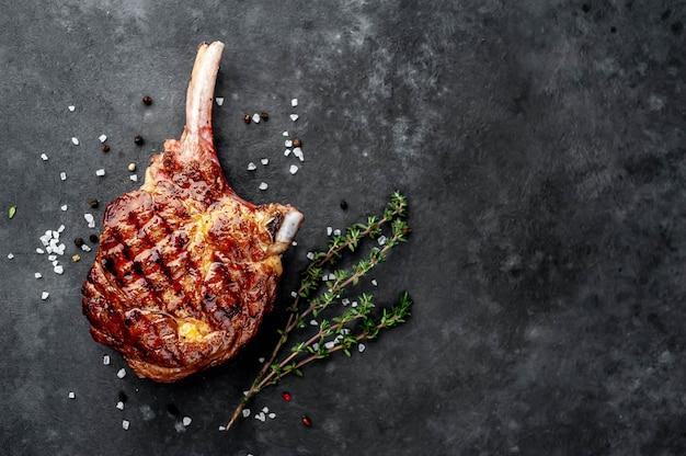 Stek - grillowana wołowina tomahawk z przyprawami, tymianek na kamiennym tle. z miejsca na kopię tekstu