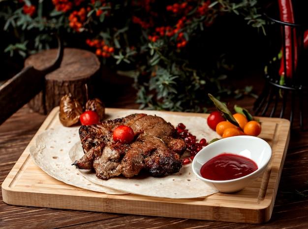 Stek jagnięcy przyozdobiony granatem, sosem kwaśnym i pomidorem
