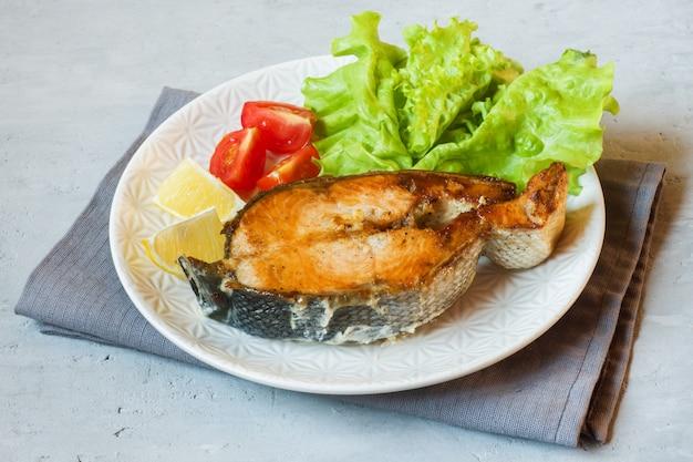 Stek łososia pieczona ryba na talerzu z świeżymi warzywami.
