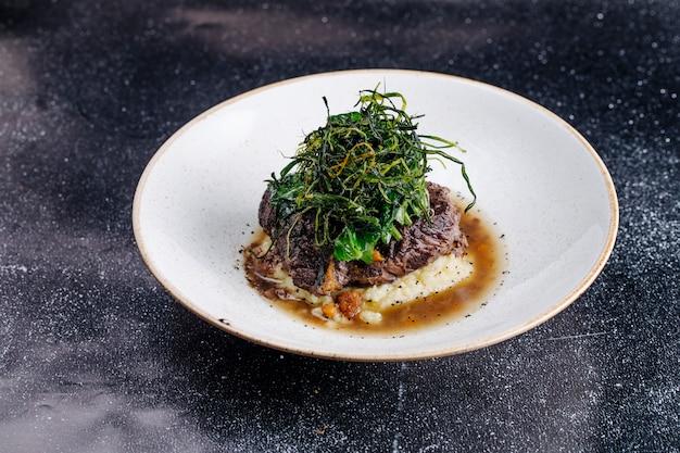 Stek mięsny z sosem bulionowym i zielenią na wierzchu.