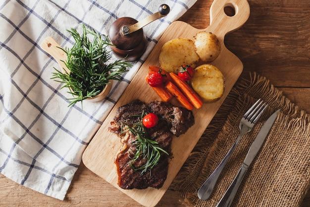 Stek na drewnianej desce do krojenia