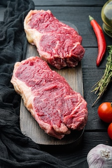 Stek nowojorski, surowe mięso wołowe, na czarnym drewnianym tle