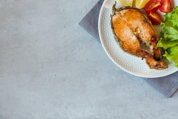 Stek pieczona ryba łosoś na talerzu ze świeżymi warzywami.