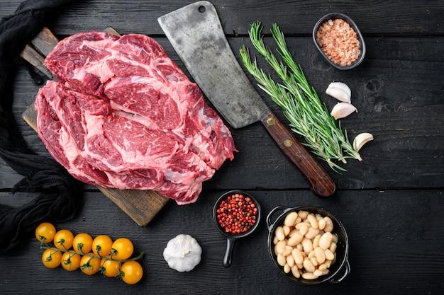 Stek ribeye karmiony surową trawą z zestawem soli i pieprzu oraz ziół i starym nożem rzeźniczym, na tle czarnego drewnianego stołu, płaski widok z góry