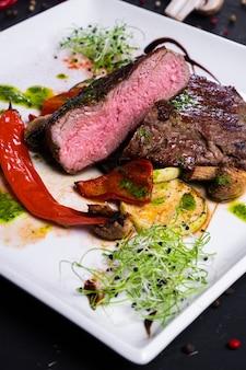 Stek ribeye z grillowanymi warzywami na białym talerzu na ciemnej powierzchni