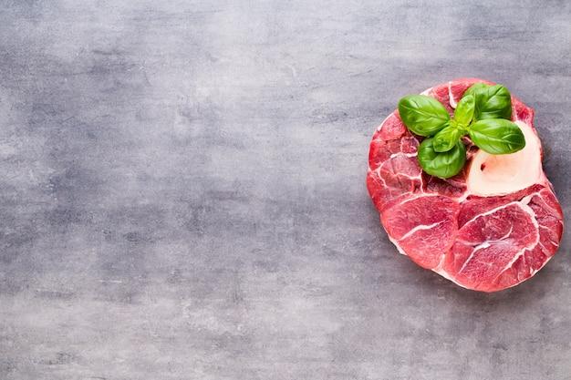 Stek ribeye z surowego mięsa wołowego z przyprawami i dodatkami.
