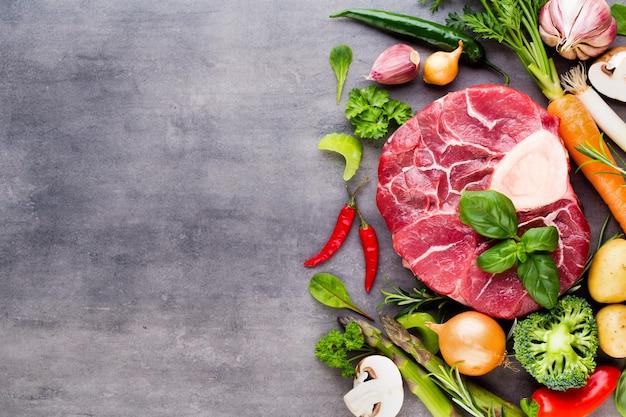 Stek ribeye z surowego świeżego mięsa wołowego z przyprawami i dodatkami.