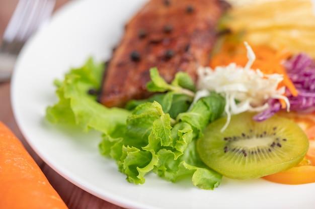 Stek rybny z frytkami, kiwi, sałatą, marchewką, pomidorami i kapustą w białym naczyniu.