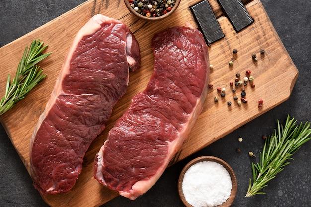 Stek, surowa wołowina ribeye z przyprawami na drewnianej desce. składniki do gotowania. widok z góry.