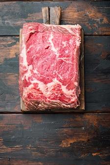 Stek veiny, marmurkowe surowe mięso wołowe, na ciemnym drewnianym stole, widok z góry
