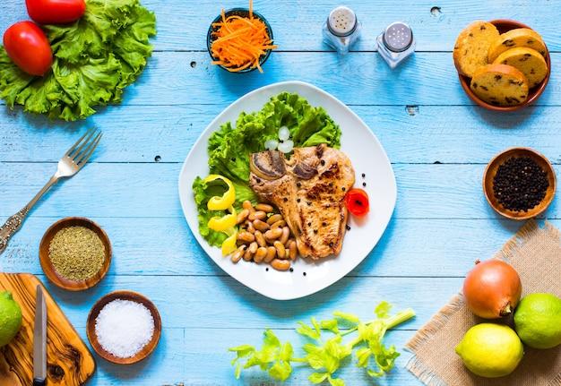 Stek wieprzowy domowej roboty gotowanie z przyprawami pozostawia sałaty na drewnianej desce do krojenia i danie,