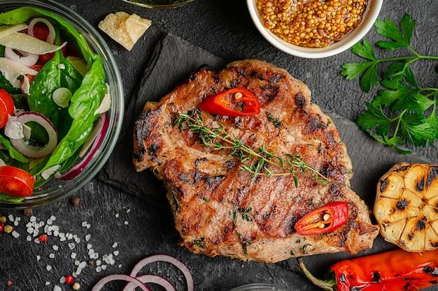 Stek wieprzowy z grilla z warzywami i sałatką na ciemnym tle