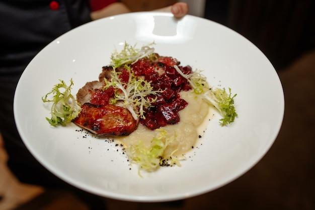 Stek wieprzowy z grilla z zieloną sałatą na drewnianym stole, widok z góry.