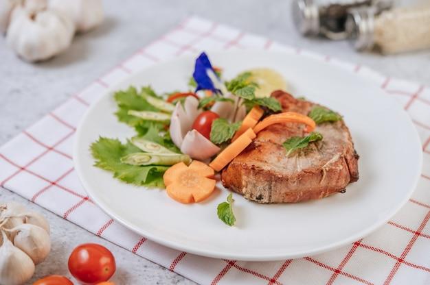 Stek wieprzowy z pomidorem, marchewką, czerwoną cebulą, miętą, kwiatem grochu motylowego i limonką.