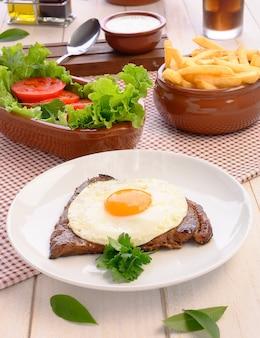 Stek wołowy (bife a cavalo) - tradycyjne potrawy brazylijskie steki, biały ryż, farofa i sałata
