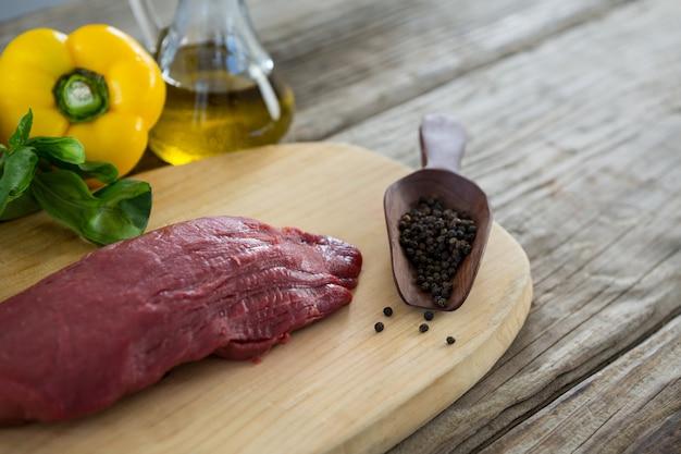 Stek wołowy i składniki na drewnianej tacy przed drewnianym stołem