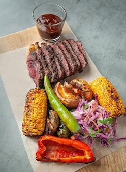 Stek wołowy jest krojony na kawałki leżący na drewnianej desce z grillowanymi pieczarkami, kukurydzą, chili i surówką. obok sosu pomidorowego. widok z góry.