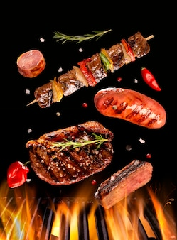 Stek wołowy, kiełbasa i szaszłyk na grillu z ogniem. brazylijski grill.