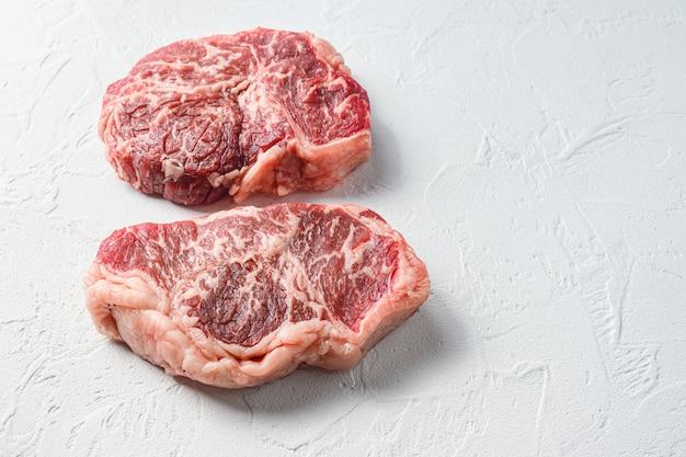Stek wołowy, mięso ekologiczne. białe tło z teksturą. widok z boku z miejscem na tekst.