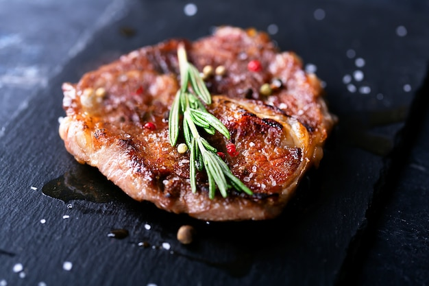 Stek wołowy na ciemnym talerzu z rozmarynem i pieprzem, selektywna ostrość