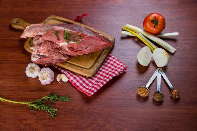 Stek wołowy na desce do krojenia w towarzystwie cebuli, pomidora, czosnku i różnych przypraw