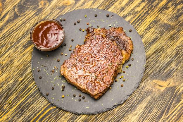 Stek wołowy na drewnianym stole. soczysty stek z wołowiny.