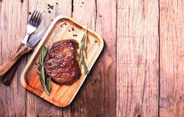 Stek wołowy na drewnianym talerzu z rozmarynem i pieprzem, widok z góry