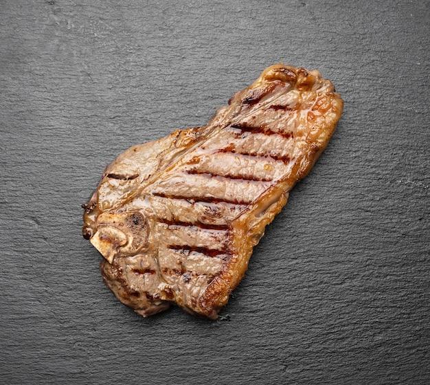 Stek wołowy nowojorski w całości smażony na czarnej desce, rostbef rzadki, widok z góry