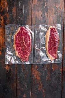 Stek wołowy picanha do gotowania sous vide na ciemnym starym drewnianym stole, widok z góry z miejscem na tekst.