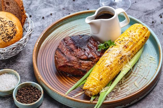 Stek wołowy podawany z grillowaną kukurydzą i sosem