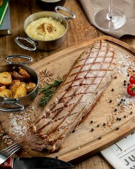 Stek wołowy podawany z ziemniakami, doprawiony koszerną solą
