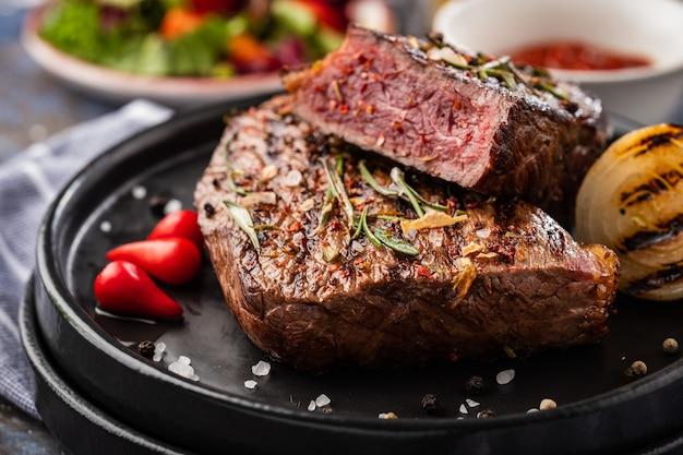 Stek wołowy. średni stek wołowy z czerwoną papryką, aromatycznymi ziołami i smażoną cebulą