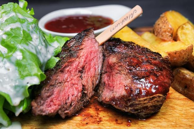 Stek wołowy z frytkami i sałatą na drewnianej desce